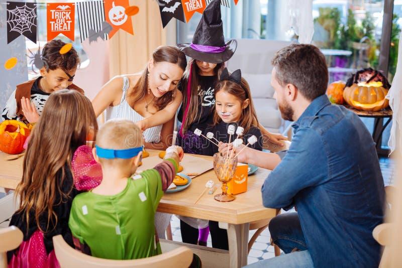 Att älska uppfostrar behandling av deras barn som bär allhelgonaaftondräkter med sötsaker arkivbild
