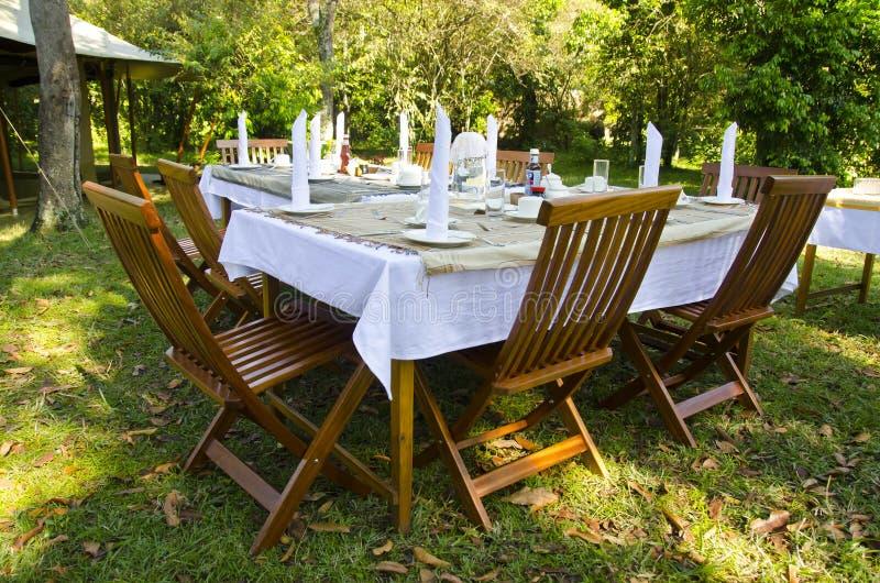 Att äta middag bordlägger uppsättningen i frodig trädgård royaltyfri bild