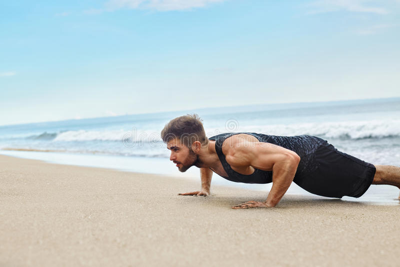 Att öva för man som gör skjuter upp övningar på stranden Konditiongenomkörare royaltyfria bilder