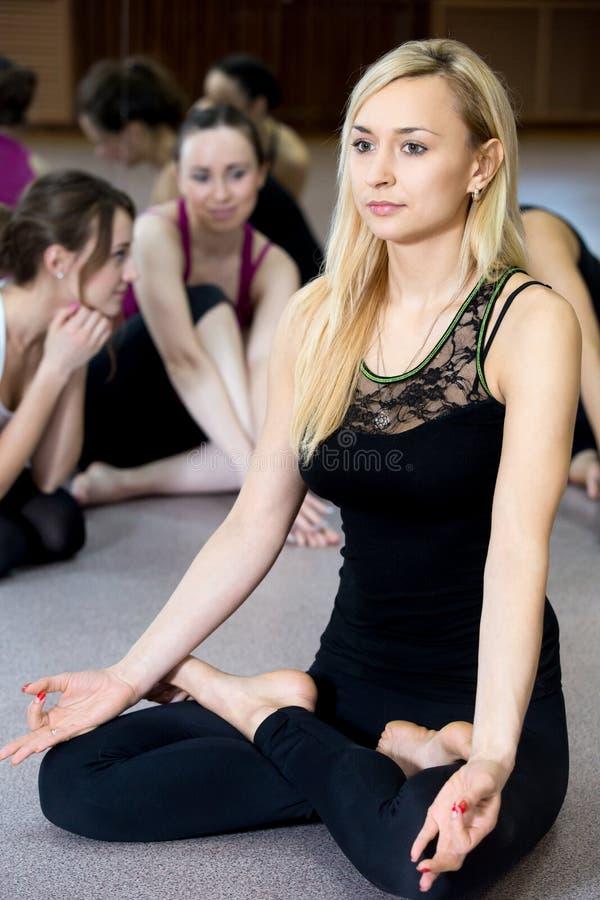 Att öva för yogiflicka som gör yoga, poserar sukhasana royaltyfria bilder