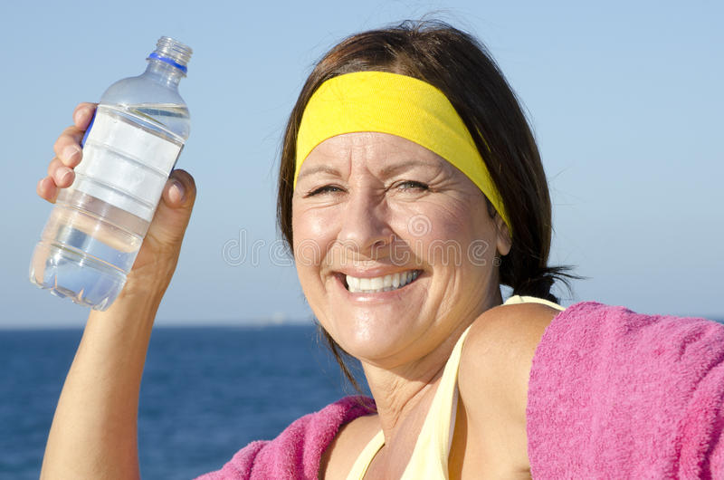 Att öva mognar kvinnadricksvatten arkivfoto