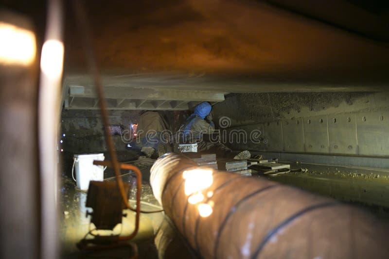 Att använda evakuera ventilationssystemet fläktar säkerhetsförsiktighet, medan reptillträdesgruvarbetare som börjar oxy facklakli royaltyfri fotografi