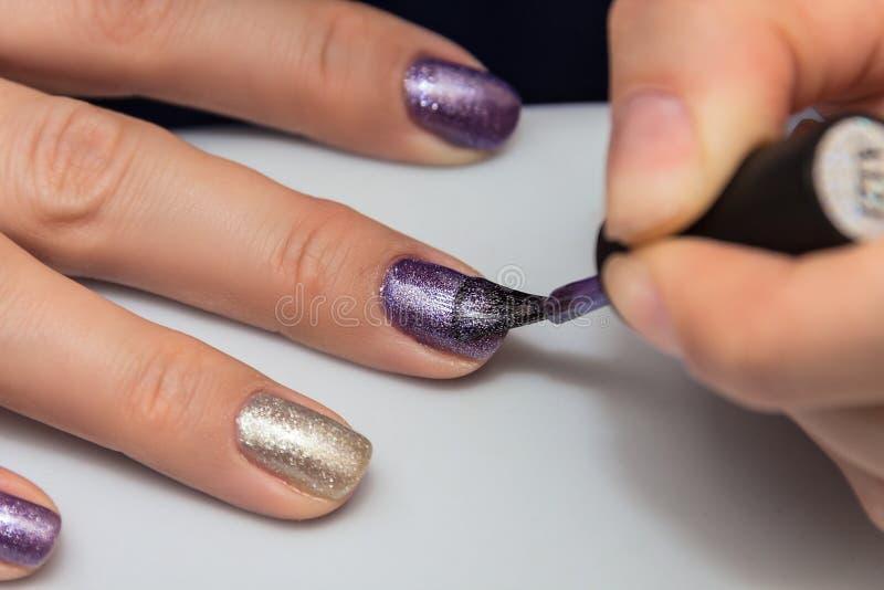 Att applicera stelnar spikar polermedel på spikar av fingrarna fotografering för bildbyråer