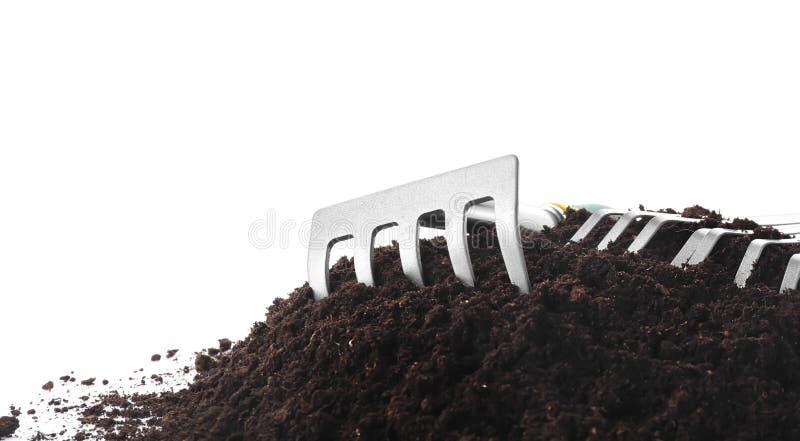 Att arbeta i trädgården krattar med jord på vit bakgrund royaltyfria foton