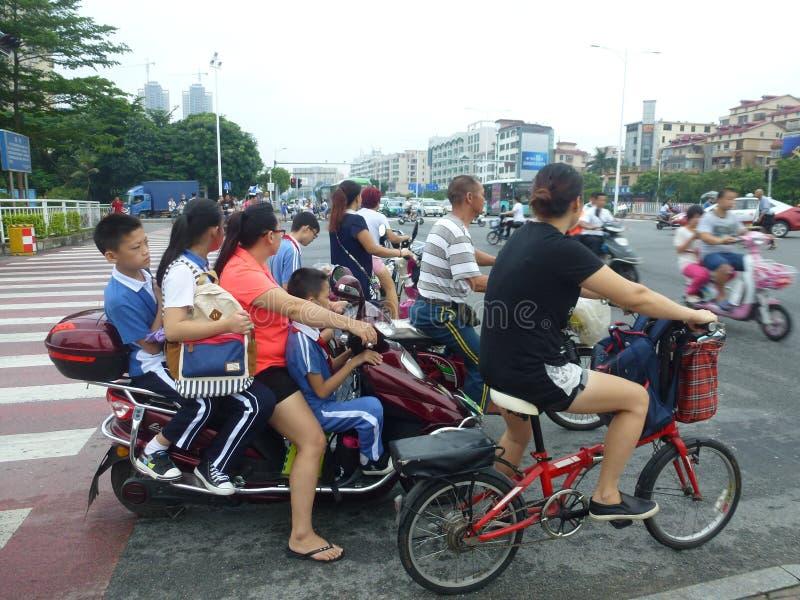 Att att överföra deras barn till skolan med elektriska cyklar och att överlasta arkivfoto