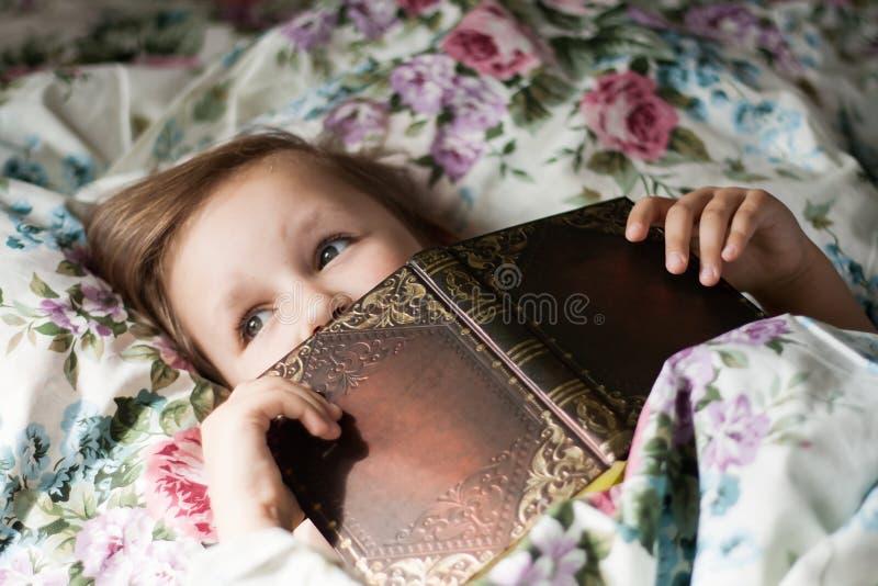 Att att läsa att ligga i en säng royaltyfri bild