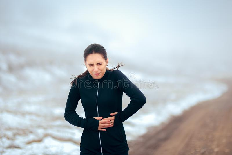 Att avverka för kvinna smärtar, medan köra i vinterförkylning royaltyfri foto