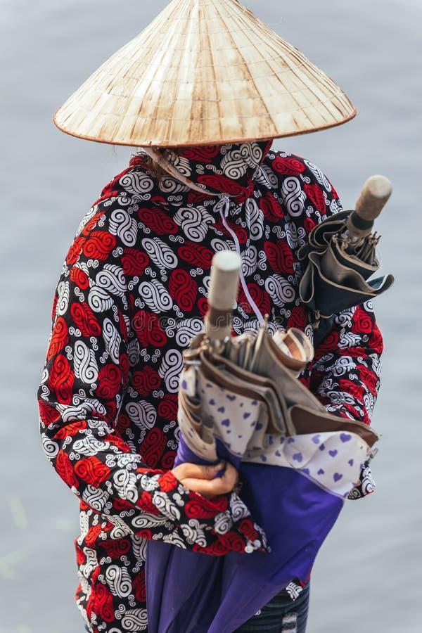 Att bära för ekakvinna som är rött, och vit färgar skjortan, den koniska hatt- och munmaskeringsställningen och bär paraplyer i N fotografering för bildbyråer