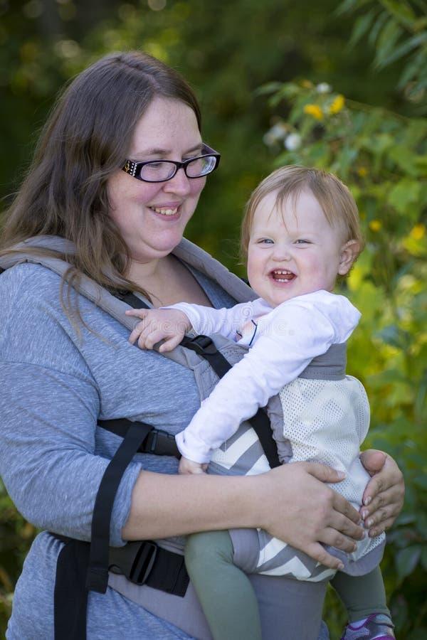 Att bära för mamma behandla som ett barn flickan med bäraren som tycker om dagen i parkera royaltyfri fotografi