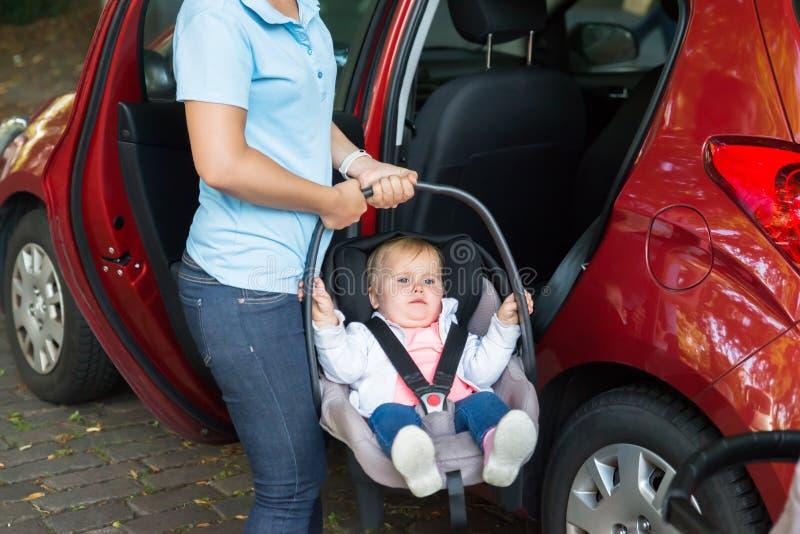 Att bära för moder behandla som ett barn på bilsätet arkivfoton