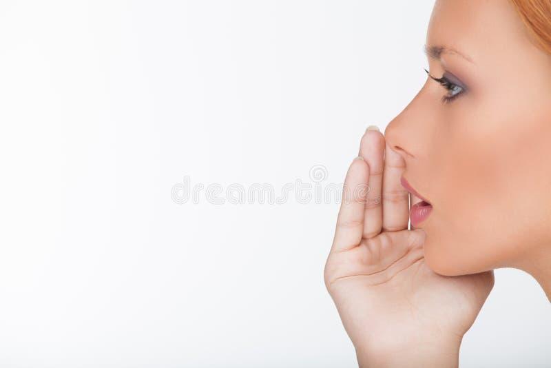 Att berätta skvallrar. Närbild av den härliga unga kvinnan som berättar t fotografering för bildbyråer