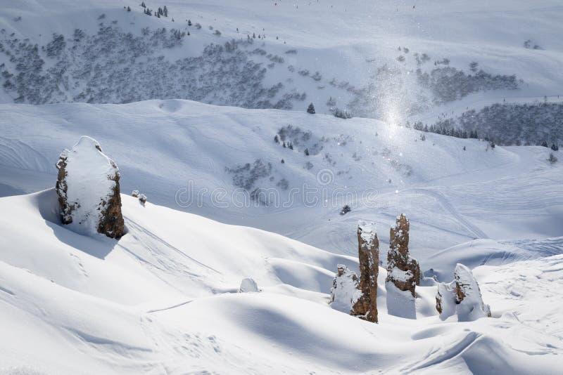 Att blänka snöflingor ovanför vaggar på en härlig solig dag i ursprungligt alpint landskap Lugna och stillsamt vinterlandskap fra royaltyfri foto