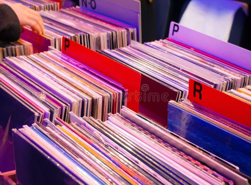 Att bl?ddra till och med gamla vinylrekord i musik shoppar bakgrund ?r kan olika anv?nda illustrationmusikavsikter royaltyfri bild