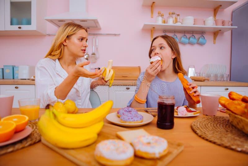 Att bry sig äldre syster som berättar hennes sibling att inte äta många munkar royaltyfri bild