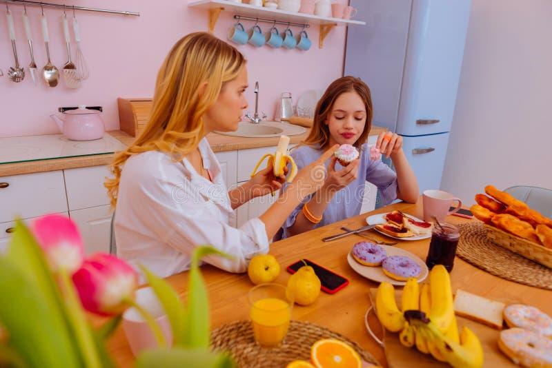 Att bry sig äldre syster som berättar hennes sibling om sunt, banta royaltyfria bilder