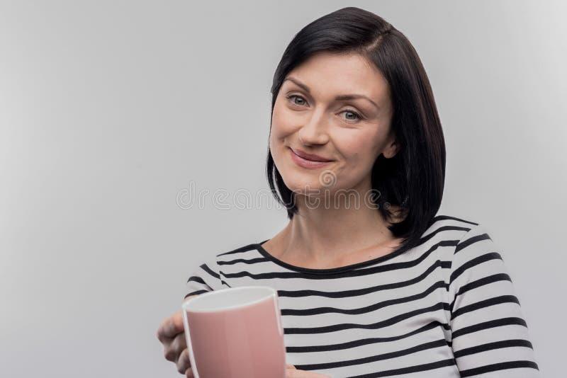 Att bry sig den erbjudande kopp te för mörker-haired fru hennes älska make arkivbild
