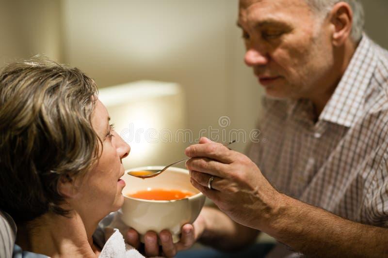 Att bry sig den höga mannen som matar hans sjuka fru royaltyfria bilder