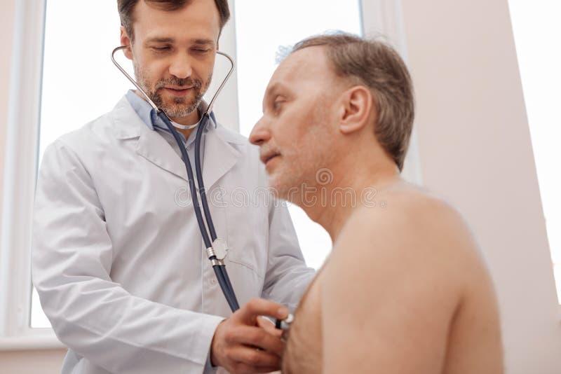 Att bry sig den kompetenta doktorn se till hans patient som är sund royaltyfria bilder