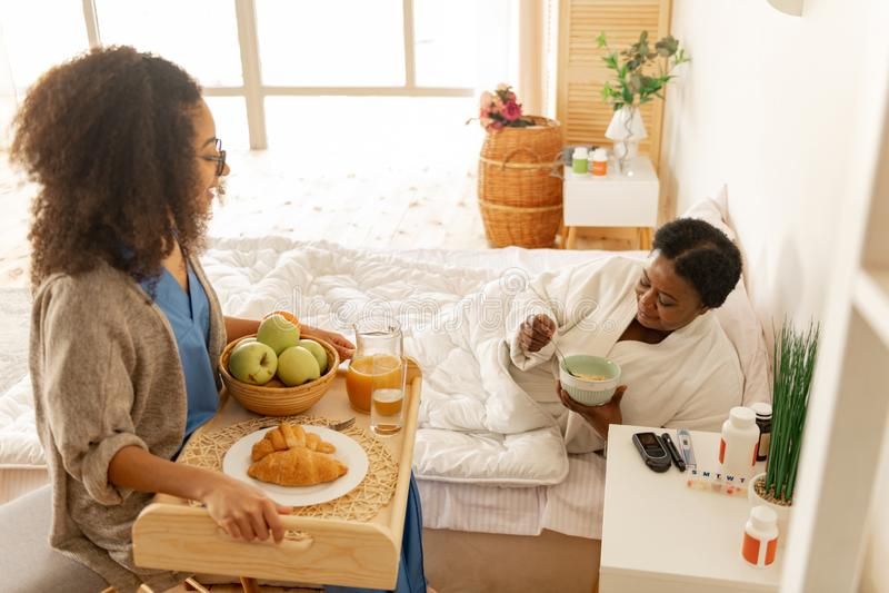 Att bry sig den lockiga sjuksk?terskan som kommer med magasinet med frukosten f?r patient royaltyfria foton
