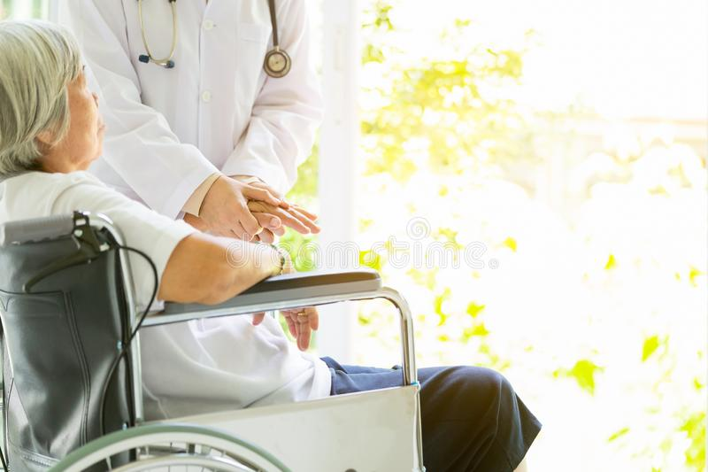 Att bry sig doktorn eller sjuksköterskan som stöttar den rörelsehindrade höga asiatiska kvinnan på rullstolen i sjukhus, kvinnlig royaltyfri bild