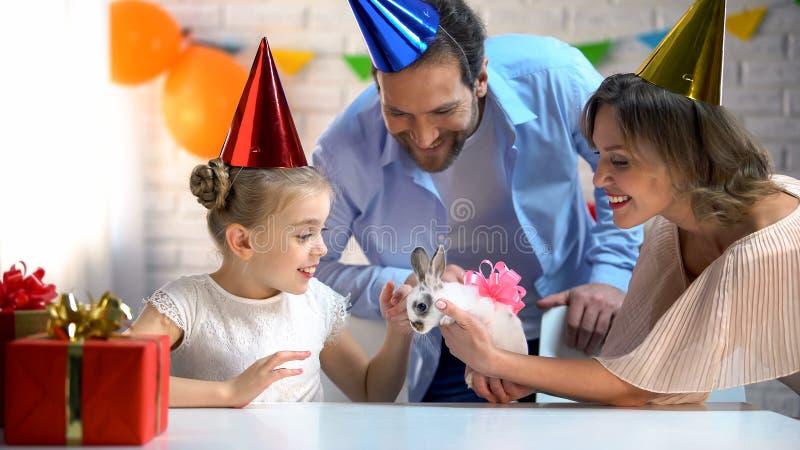 Att bry sig föräldrar som gör överraskning till den lilla dottern som framlägger den lilla gulliga kaninen fotografering för bildbyråer