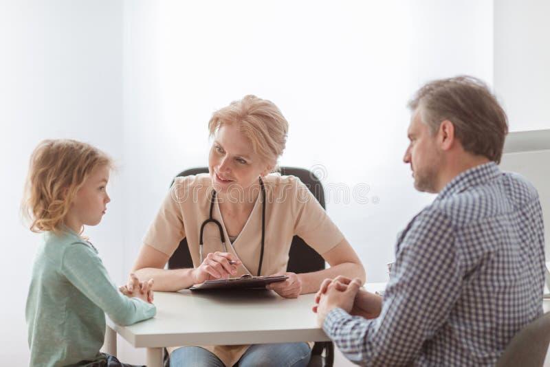 Att bry sig fadern med den gulliga lilla sonen under tidsbest?llning med pediatriskt arkivfoton