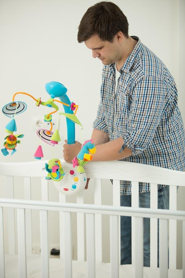 Att bry sig fadern som monterar, behandla som ett barn kåtan för ` s och att sätta leksakkarusell in royaltyfri bild