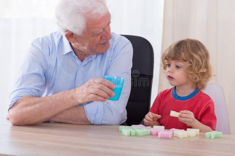 Att bry sig farfadern och det gulliga barnbarnet royaltyfria bilder