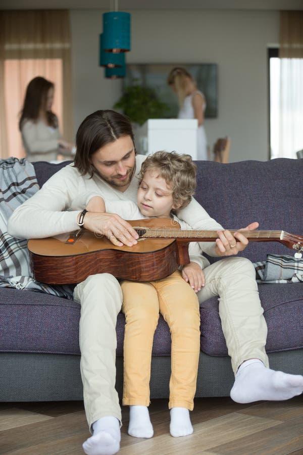 Att bry sig farsaundervisning lura sonen för att spela gitarren hemma royaltyfria foton