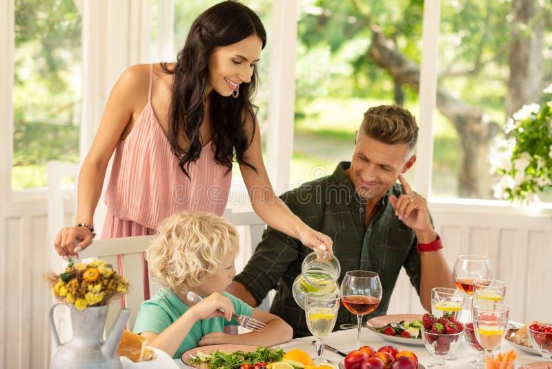 Att bry sig hällande lemonad för mamma för hennes älskvärda blonda son royaltyfri foto