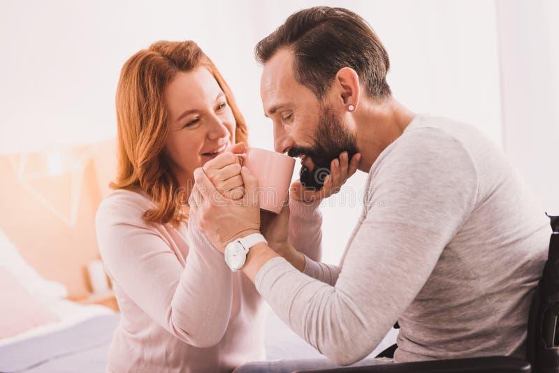 Att bry sig kvinnan som hjälper hennes make att dricka arkivfoton