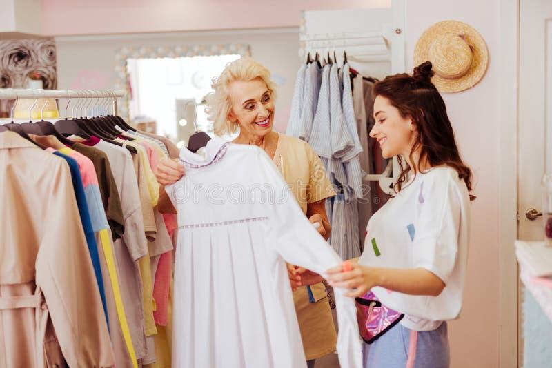 Att bry sig le modern som visar hennes dotter den stilfulla klänningen royaltyfri foto