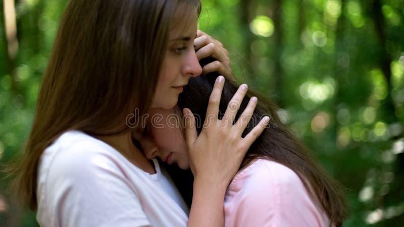 Att bry sig lesbiska kvinnan som tröstar henne uppriven flickvän, ömsesidig överenskommelse, service royaltyfri fotografi