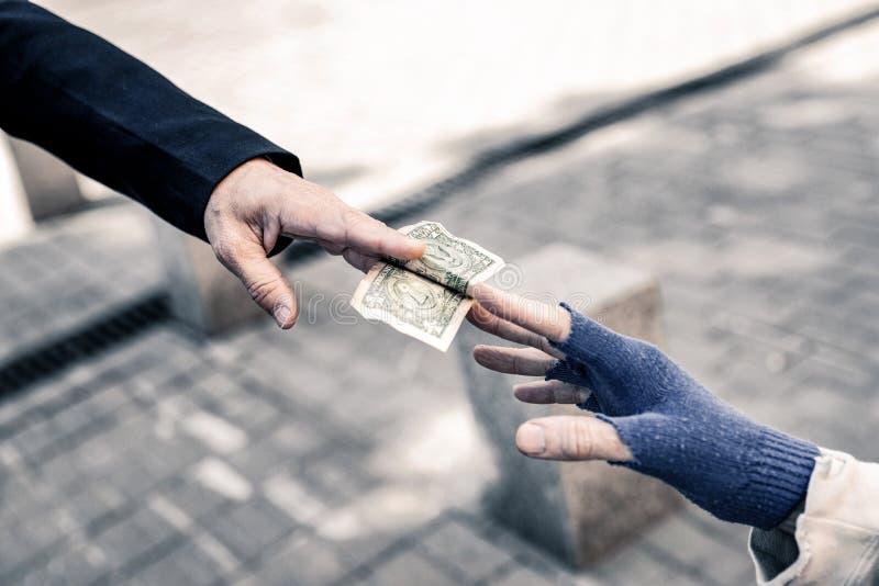 Att bry sig mannen som sätter pengar i händer av den nödvändiga gamala mannen royaltyfri fotografi