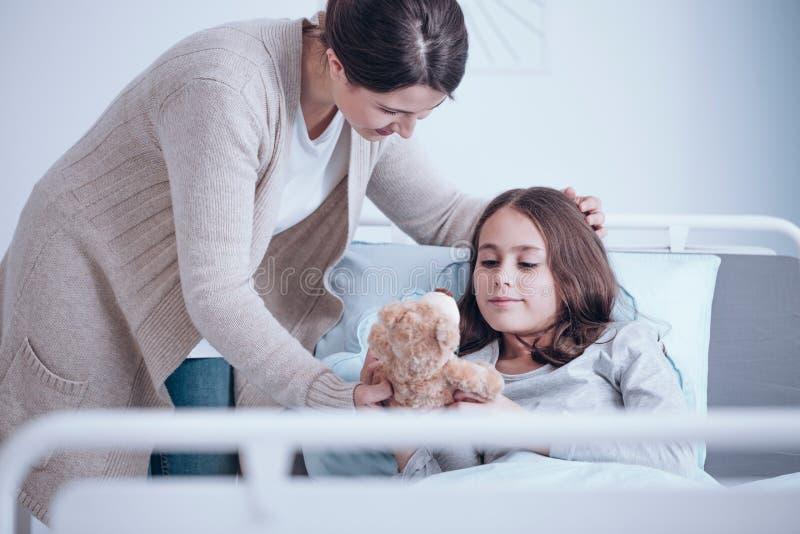 Att bry sig modern och den sjuka dottern royaltyfri bild