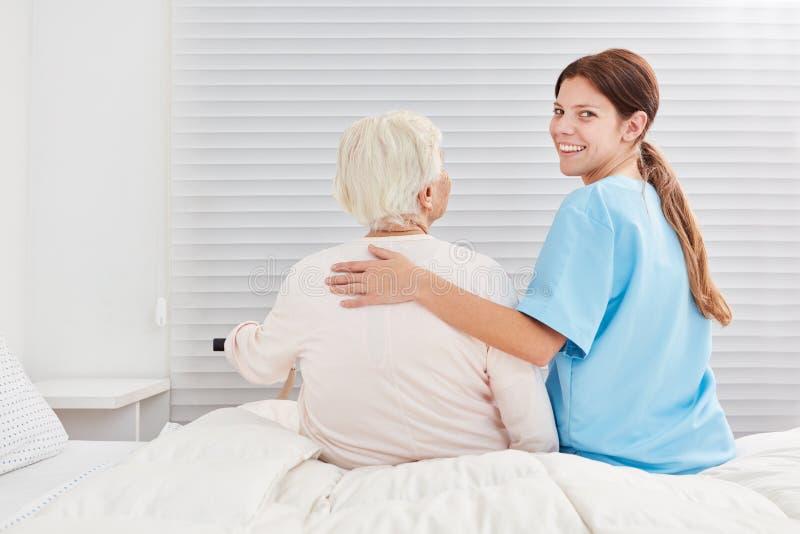 Att att bry sig omsorghjälp hjälper pensionären ut ur säng royaltyfri fotografi