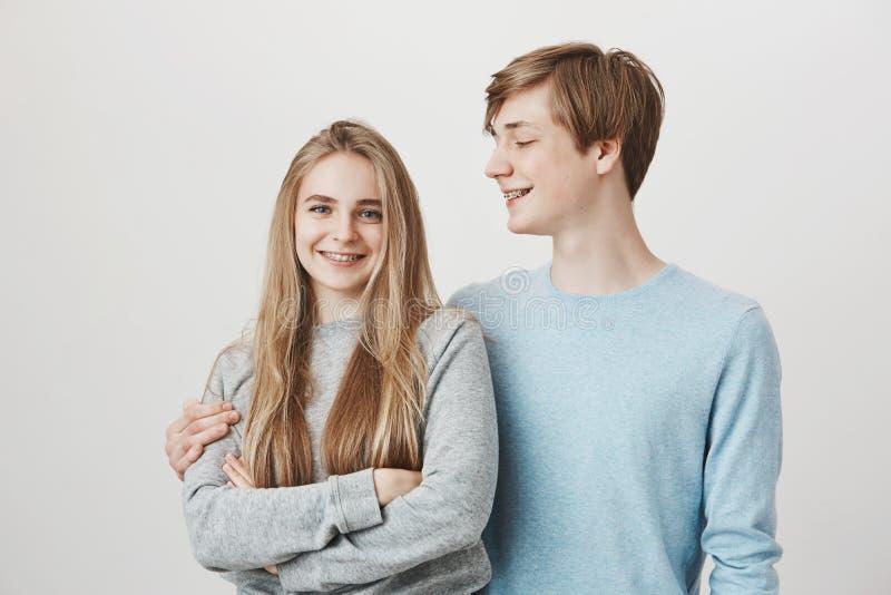 Att bry sig pojkvännen älskar allt i henne Högväxt attraktiv ung grabb med ganska hår som kramar och ser flickvännen arkivfoton