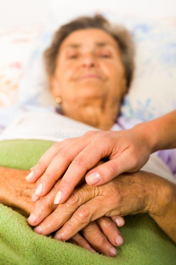 Att bry sig sjuksköterskan Holding Hands royaltyfria bilder