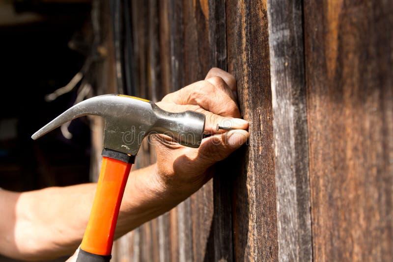 Att att bulta för att spika med en hammare Äldre arbetarsnickare royaltyfri bild