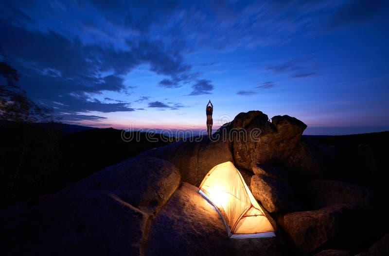 Att campa på vaggar bildande Tält- och turistflickaanseende med lyftta armar på bergöverkant arkivfoton