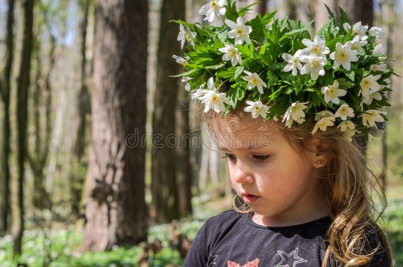 Att charma behandla som ett barn flickan med en krans av vita blommor på hennes huvud, medan gå i skogen på en solig eftermiddag royaltyfria bilder