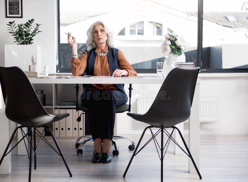 Att charma den åldriga yrkesmässiga kvinnlign är att arbeta i ljust kontor royaltyfri foto