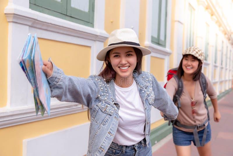 Att charma den härliga handelsresandekvinnan rymmer hand'svännen och den inviterande vännen till något touristic ställe De ser  royaltyfria bilder