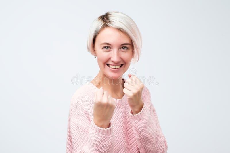 Att charma den roliga caucasian kvinnan i den rosa tröjan som lyfter nävar och att stå i boxare, poserar och att önska att stansa royaltyfria bilder