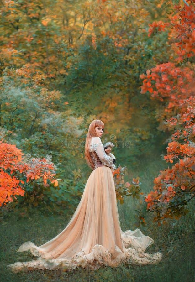 Att charma den ursnygga flickan med brännhett rött hår står bara i höstskog i den långa ljusa chic klänningklänningen som rymmer  arkivfoto