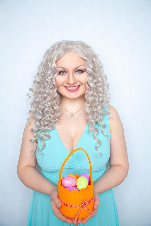 Att charma le blondintonåringen står i en blå klänning med en orange korg med målade ägg för påsk bara på vit studio s royaltyfria bilder