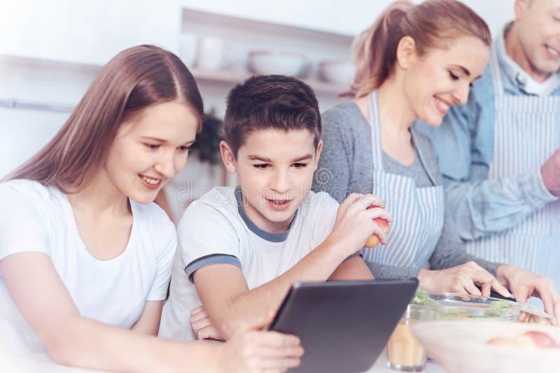 Att charma lurar att spela på den digitala minnestavlan medan att laga mat för föräldrar royaltyfri fotografi