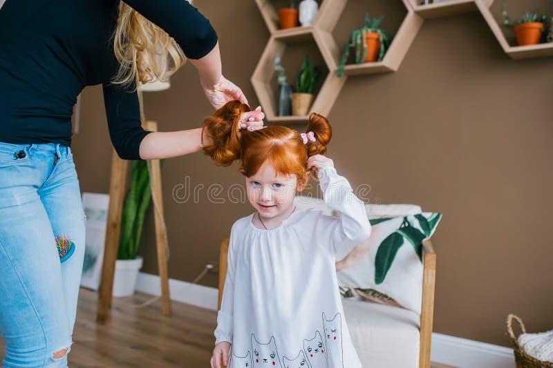Att charma rödhårig manlilla flickan ser kameran och ler, medan hennes moder kammar dotterns hår royaltyfri fotografi