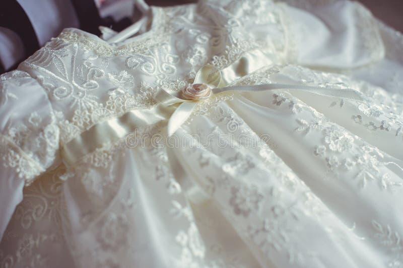 Att döpa behandla som ett barn klänningen Närbilden av ett gulligt nyfött behandla som ett barn klänningen Stilfull broderad vit  arkivfoto