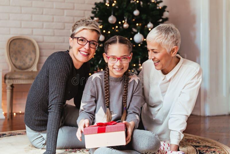 Att dekorera för farmor och för sondotter jul samlade treeFamily runt om en julgran, kvinnliga utvecklingar royaltyfria foton